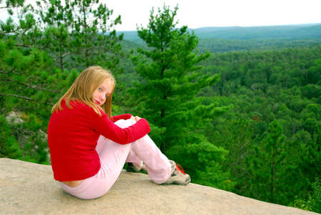 Young girl sitting on an edge of a cliff photo
