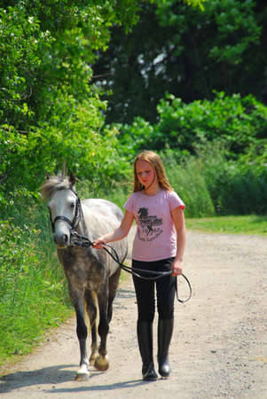 Young girl walking with a pony on a farm road photo