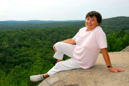 cliff edge: Mature woman sitting on scenic cliff edge smiling