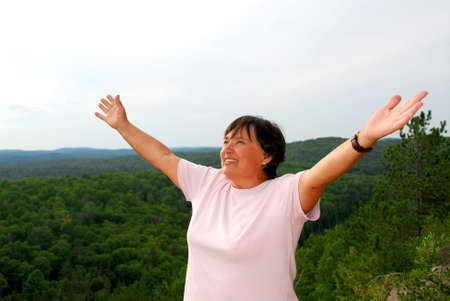 hilltop: Mature woman on hilltop raising her arms Stock Photo