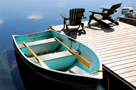 adirondack chair: Two wooden adirondack chairs on a boat dock on a beautiful still lake with sky reflection