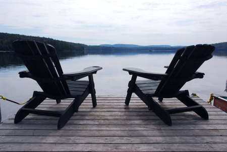 Two wooden adirondack chairs on a boat dock on a beautiful lake in the evening photo