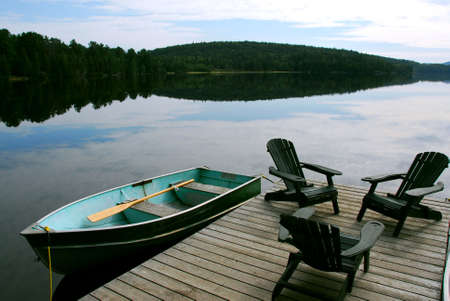 adirondack chair: Three wooden adirondack chairs on a boat dock on a beautiful lake in the evening