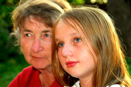 Portrait of grandmother and granddaughter in summer park, focus on the girl