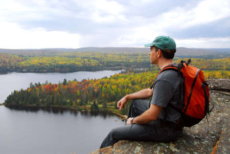 A hiker sitting on a cliff edge enjoying scenic view Stock Photo