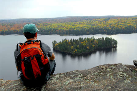 cliff edge: A hiker sitting on a cliff edge enjoying scenic view Stock Photo