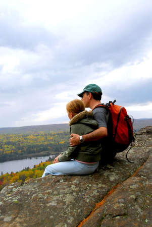 A parent and a child sitting on a cliff edge enjoying scenic view photo