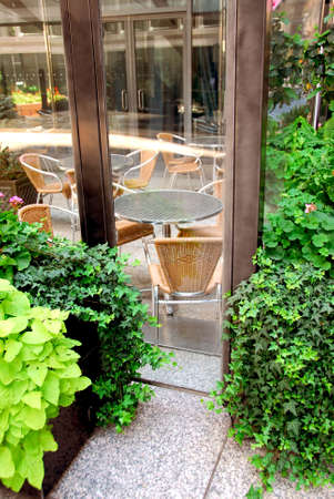 Restaurant outdoor patio behind glass walls with green plants