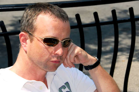 Portrait of a thoughtful man wearing sunglasses in outdoor cafe photo