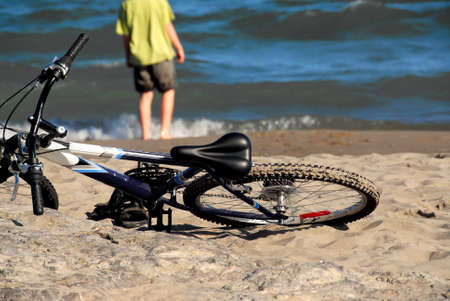 Boy a piedi in acqua con la sua bicicletta giace su una spiaggia