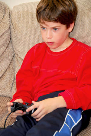 xbox: Young boy playing a video game sitting on a couch