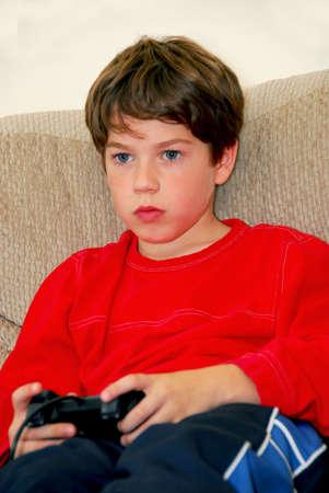 Jongen het afspelen van een video game zit op een bank Stockfoto