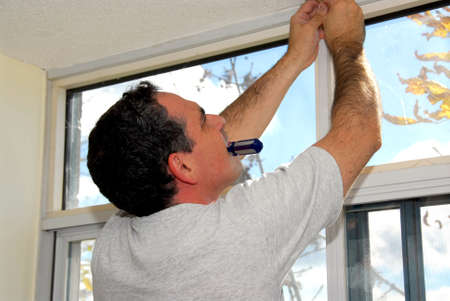 blinds: Man installing window blinds in a house