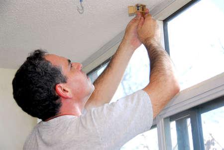 stores: Homme installant des abat-jour de fen�tre dans une maison Banque d'images