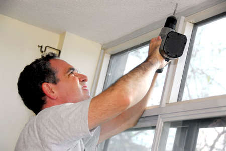 window treatments: Man drilling a hole in a ceiling Stock Photo