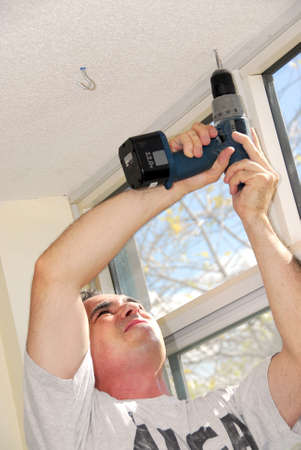 Man drilling a hole in a ceiling Stock Photo