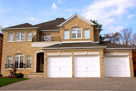 garage on house: New detached single family luxury home with stone facade and tripple garage