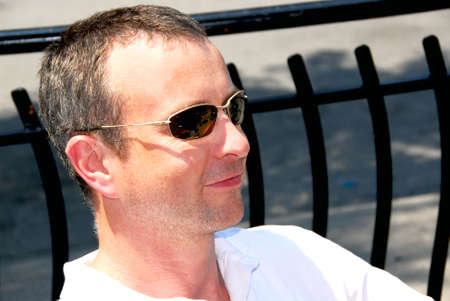 Portrait of a smiling man wearing sunglasses in outdoor cafe photo