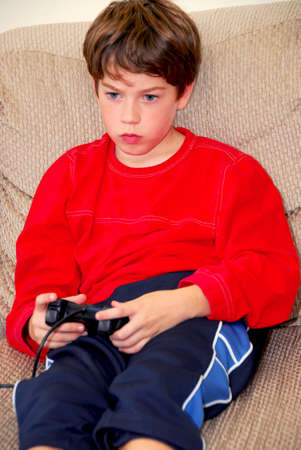 Young boy playing a video game sitting on a couch