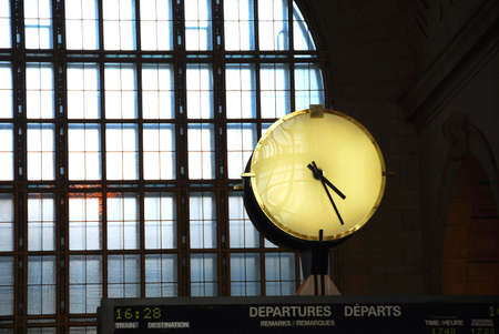 Big clock inside a train station on top of the time table photo