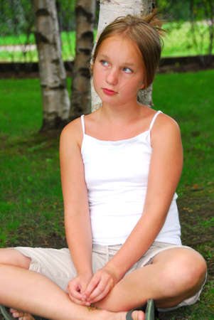 top: Portrait of a young pretty girl sitting under a birch tree in a park