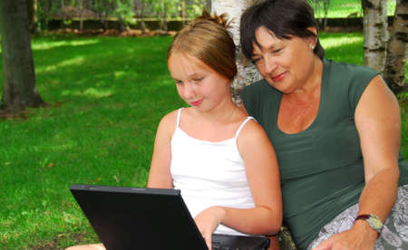 Grandmother and granddaughter sitting outside with laptop computer photo
