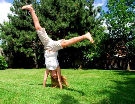 Young girl doing a cartwheel on green grass photo