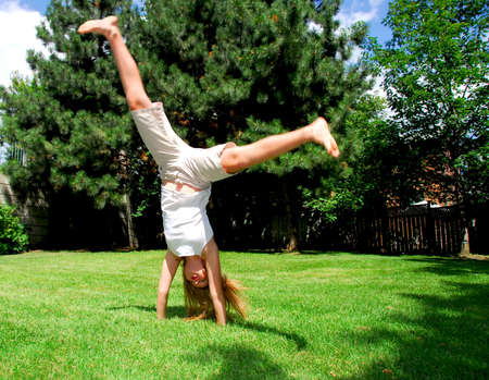 Young girl doing a cartwheel on green grass Stock Photo