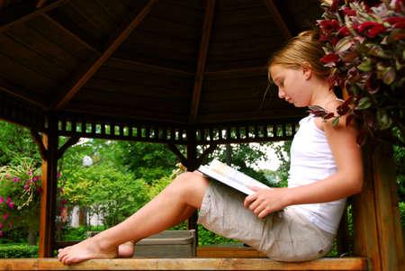 scalzo ragazze: Ragazza seduta in un gazeebo la lettura di un libro  Archivio Fotografico