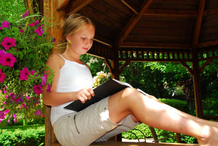 Young girl sitting in a gazeebo reading a book photo