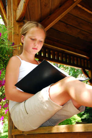 beautiful preteen girl: Young girl sitting in a gazeebo reading a book