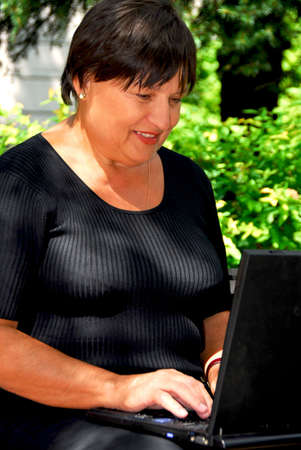 Mature woman working on laptop computer outdoors photo