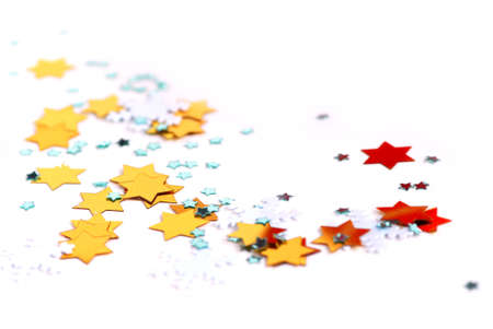 Christmas background of scattered gilittering confetti on white photo