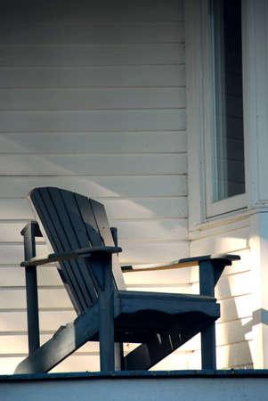 silla de madera: Silla de madera iluminado por el sol en un porche de una casa  Foto de archivo
