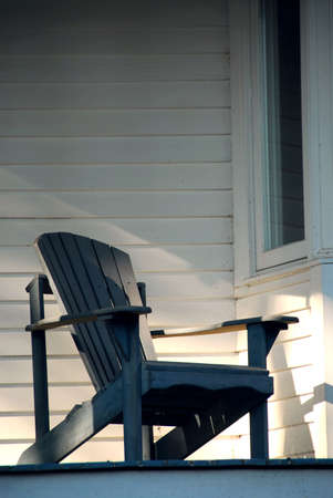 Wooden chair on a sunlit porch of a house Stock Photo - 582869