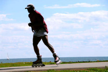 Man rollerblading on sea shore trail, motion blur