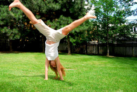 Young girl doing a cartwheel on green grass photo