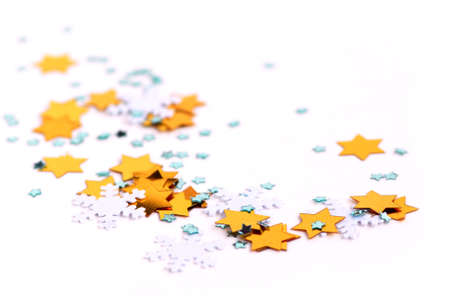 scattered: Christmas background of scattered gilittering confetti on white