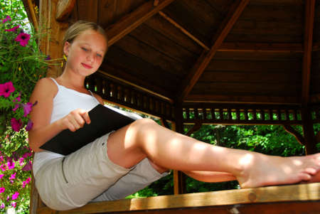 freckles: Young girl sitting in a gazeebo reading a book