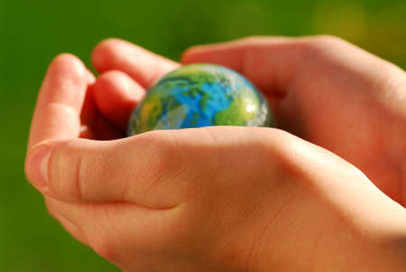 Childs hands holding a globe on green background photo