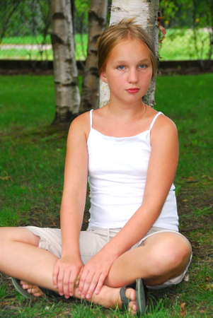 cross leg: Portrait of a young pretty girl sitting under a birch tree in a park