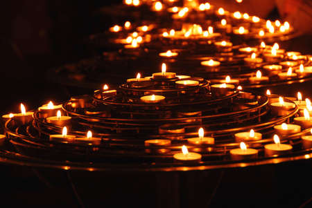 Rows of burning candles inside a cathedral