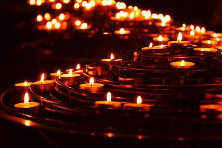 mystique: Rows of burning candles in a cathedral