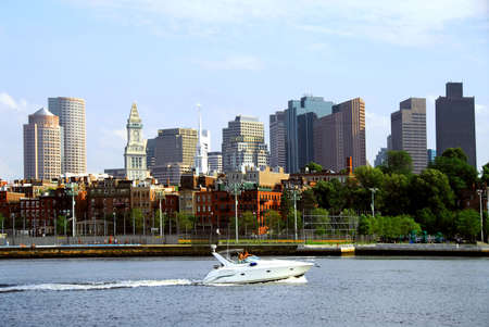 boston skyline: Motorboat in a harbor in front of a Boston skyline on a sunny summer day