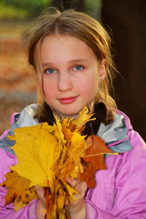 Young girl holding a pile of autumn maple leaves photo