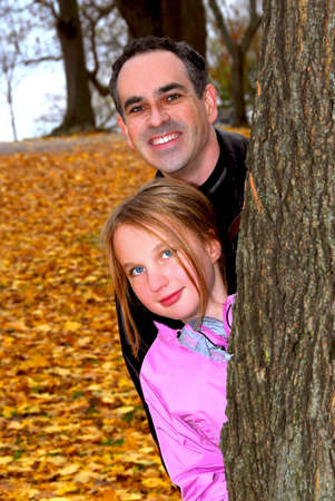 peaking: Father and daughter peaking from a tree trunk in autumn park Stock Photo
