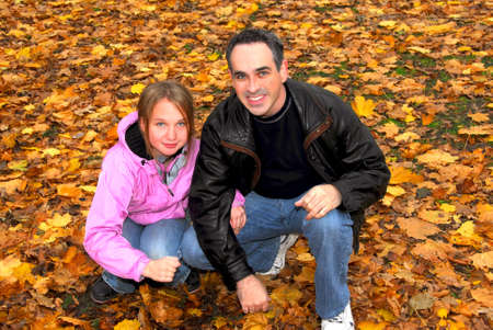 Father and daughter playing in autumn park photo