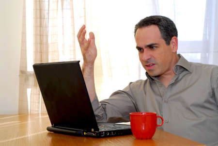 Man sitting at a desk and looking into his computer Stock Photo