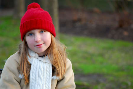 Portrait of a young girl sitting on a bench photo