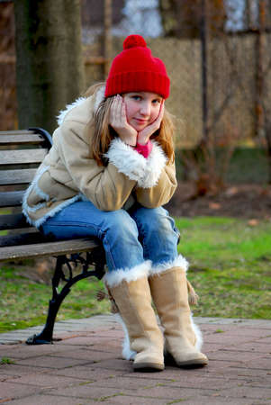 Portrait of a young girl sitting on a bench outside photo